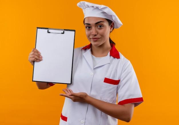 Het jonge zekere kaukasisch kokmeisje in eenvormige chef-kok houdt klembord en punten met hand die op oranje muur met exemplaarruimte wordt geïsoleerd