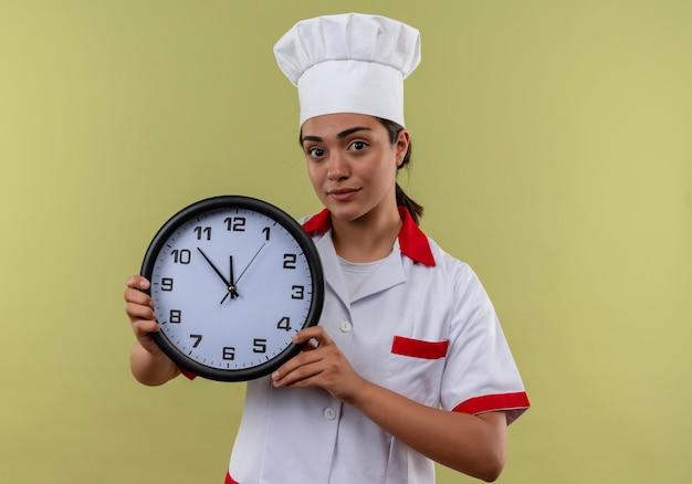 Het jonge zekere kaukasisch kokmeisje in eenvormige chef-kok houdt klok die op groene muur met exemplaarruimte wordt geïsoleerd