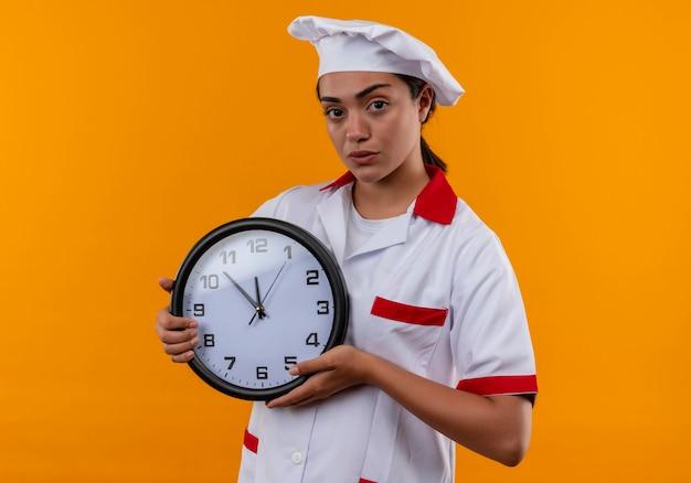 Het jonge zekere kaukasisch kokmeisje in eenvormige chef-kok houdt klok met beide die handen op oranje muur wordt geïsoleerd