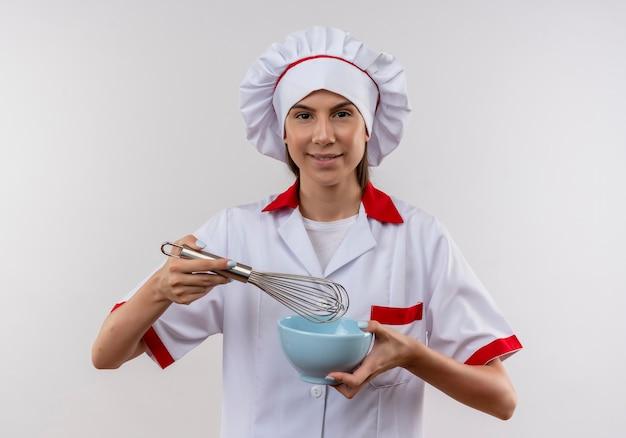 Het jonge zekere kaukasisch kokmeisje in eenvormige chef-kok houdt klop en kom op wit met exemplaarruimte
