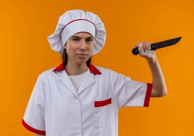 Het jonge zekere kaukasisch kokmeisje in eenvormige chef-kok houdt mes op sinaasappel met exemplaarruimte