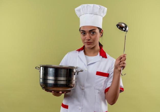 Het jonge zekere kaukasisch kokmeisje in eenvormige chef-kok houdt pot en pollepel die op groene muur met exemplaarruimte wordt geïsoleerd