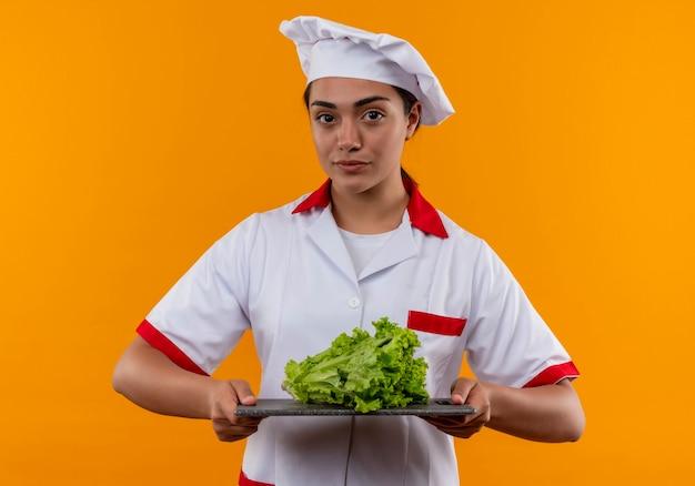 Het jonge zekere kaukasisch kokmeisje in eenvormige chef-kok houdt salade op scherp bureau dat op oranje muur met exemplaarruimte wordt geïsoleerd