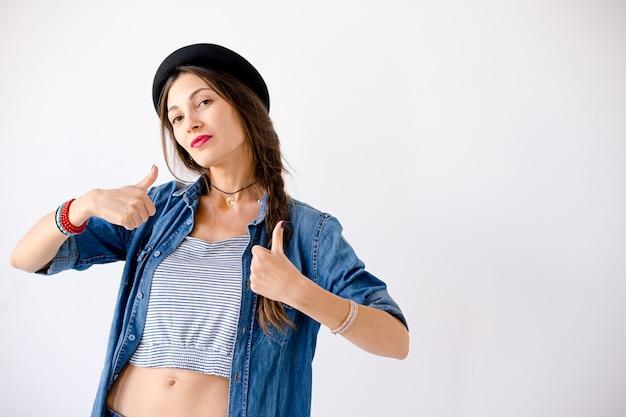 Het jonge zekere vrouwenportret die hoed het tonen dragen beduimelt omhoog