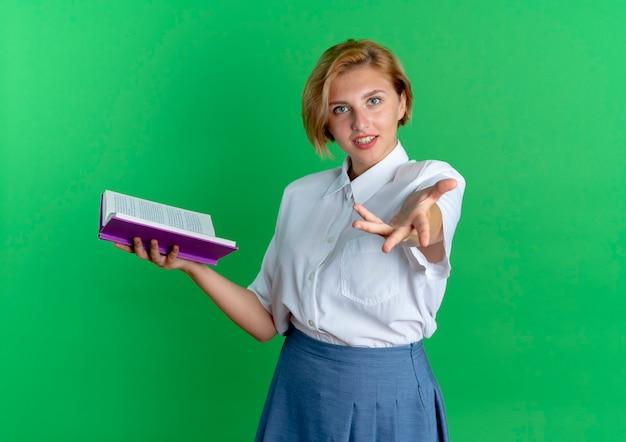 Het jonge zelfverzekerde blonde russische meisje houdt boek en steekt uit aan camera die op groene achtergrond met exemplaarruimte wordt geïsoleerd