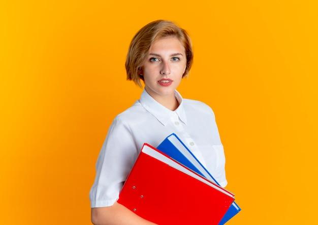 Het jonge zelfverzekerde blonde russische meisje houdt dossiermappen die camera bekijken die op oranje achtergrond met exemplaarruimte wordt geïsoleerd