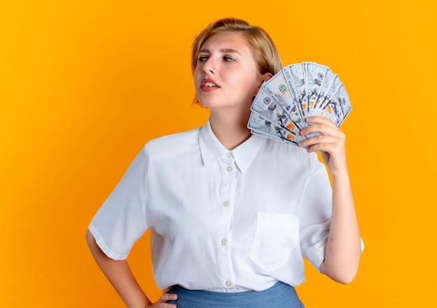Het jonge zelfverzekerde blonde russische meisje houdt geld kijkend naar kant geïsoleerd op een oranje achtergrond met kopie ruimte