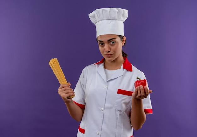 Het jonge zelfverzekerde kaukasisch kokmeisje in eenvormige chef-kok houdt bos van spaghetti en rode peper die op violette muur met exemplaarruimte wordt geïsoleerd