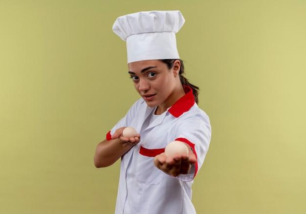 Het jonge zelfverzekerde kaukasisch kokmeisje in eenvormige chef-kok houdt eieren uit geïsoleerd op groene muur met exemplaarruimte