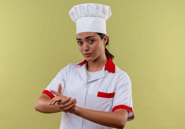 Het jonge zelfverzekerde kaukasisch kokmeisje in eenvormige chef-kok houdt handen samen geïsoleerd op groene muur met exemplaarruimte
