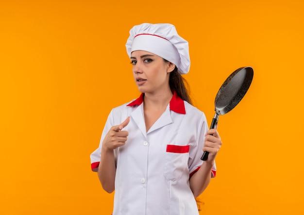 Het jonge zelfverzekerde kaukasisch kokmeisje in eenvormige chef-kok houdt koekenpan die op oranje muur met exemplaarruimte wordt geïsoleerd