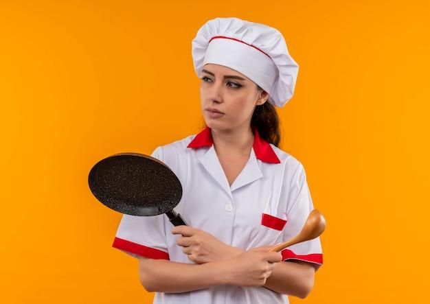 Het jonge zelfverzekerde kaukasisch kokmeisje in eenvormige chef-kok houdt koekenpan en houten lepel die op oranje muur met exemplaarruimte wordt geïsoleerd