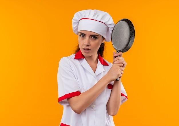 Het jonge zelfverzekerde kaukasisch kokmeisje in eenvormige chef-kok houdt koekenpan met beide handen die op oranje muur met exemplaarruimte wordt geïsoleerd