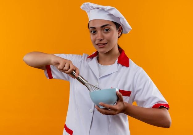 Het jonge zelfverzekerde kaukasisch kokmeisje in eenvormige chef-kok houdt kom en zwaait geïsoleerd op oranje muur met exemplaarruimte