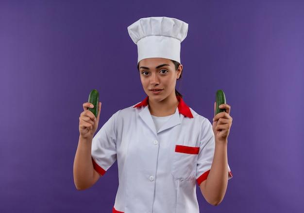 Het jonge zelfverzekerde kaukasisch kokmeisje in eenvormige chef-kok houdt komkommers in beide handen die op violette muur met exemplaarruimte worden geïsoleerd