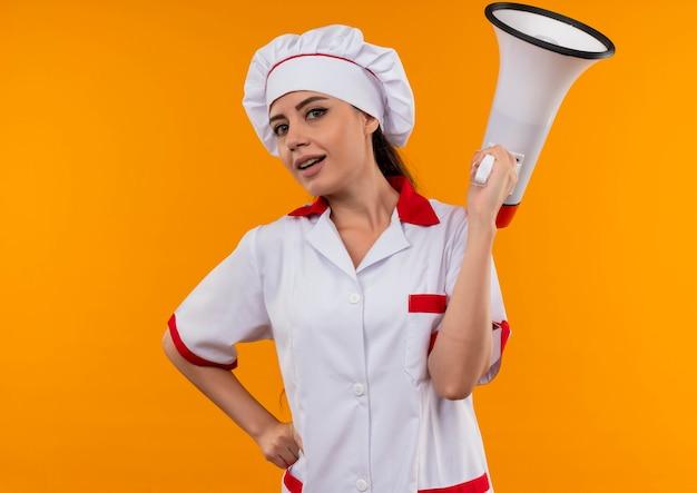 Het jonge zelfverzekerde kaukasisch kokmeisje in eenvormige chef-kok houdt luide spreker die op oranje muur met exemplaarruimte wordt geïsoleerd