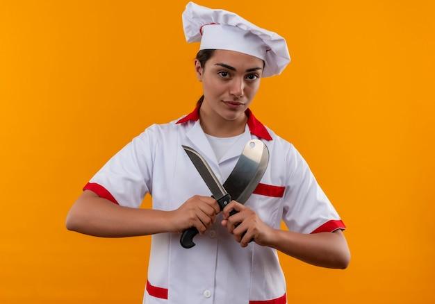 Het jonge zelfverzekerde kaukasisch kokmeisje in eenvormige chef-kok houdt messen die op oranje muur met exemplaarruimte worden geïsoleerd