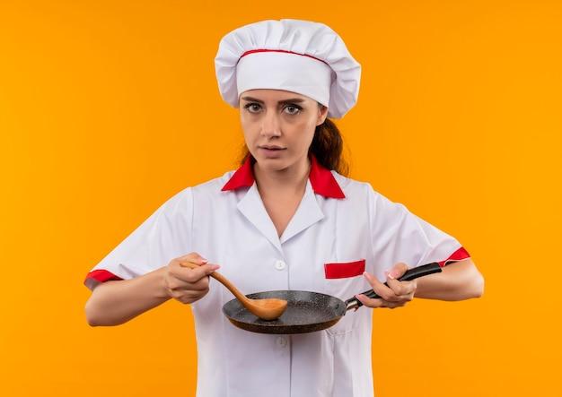 Het jonge zelfverzekerde kaukasisch kokmeisje in eenvormige chef-kok houdt pan en houten lepel die op oranje muur met exemplaarruimte wordt geïsoleerd