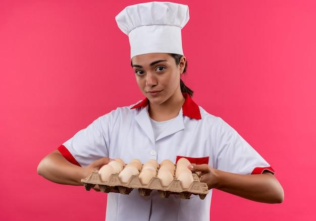 Het jonge zelfverzekerde kaukasisch kokmeisje in eenvormige chef-kok houdt partij eieren die op roze muur met exemplaarruimte worden geïsoleerd