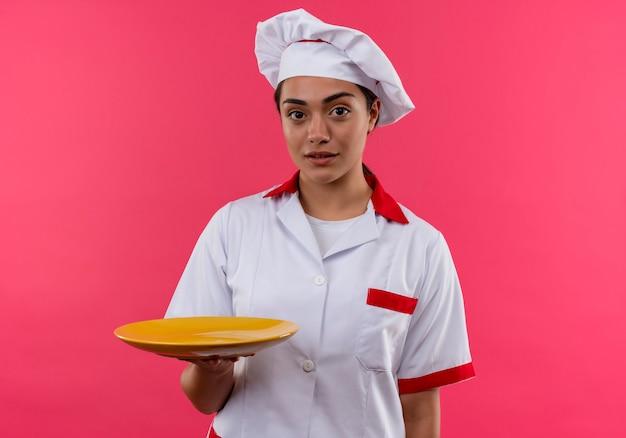 Het jonge zelfverzekerde kaukasisch kokmeisje in eenvormige chef-kok houdt plaat op roze muur met exemplaarruimte wordt geïsoleerd die