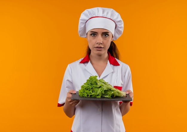 Het jonge zelfverzekerde kaukasisch kokmeisje in eenvormige chef-kok houdt salade op scherpe raad die op oranje muur met exemplaarruimte wordt geïsoleerd