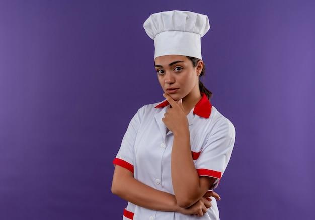 Het jonge zelfverzekerde kaukasisch kokmeisje in eenvormige chef-kok legt hand op kin die op violette muur met exemplaarruimte wordt geïsoleerd