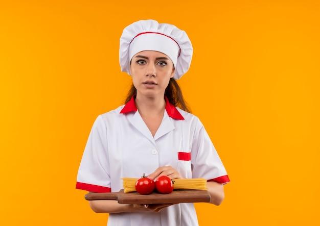 Het jonge zelfverzekerde kaukasisch kokmeisje in uniform chef-kok houdt tomaten en bos van spaghetti op scherpe raad die op oranje muur met exemplaarruimte wordt geïsoleerd