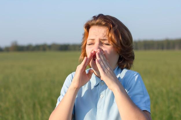 Het jonge zieke zieke meisje gaat niezen. pollen allergie concept. de vrouw voelt zich onwel, slecht in een zomergebied. griep, verkoudheid of een virus hebben bij zonnig weer.