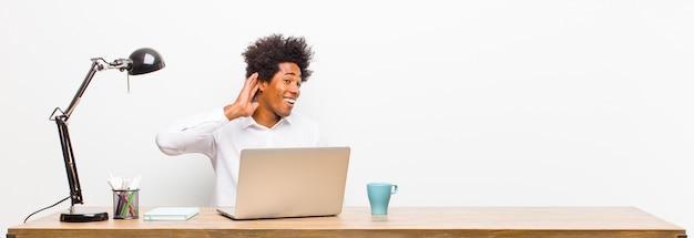 Het jonge zwarte zakenman glimlachen, die nieuwsgierig aan de kant kijken, proberen te roddelen of een geheim op een bureau afluisteren