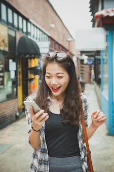 Het jongere bericht van de aziatische vrouwenlezing in slimme telefoon met gelukgezicht