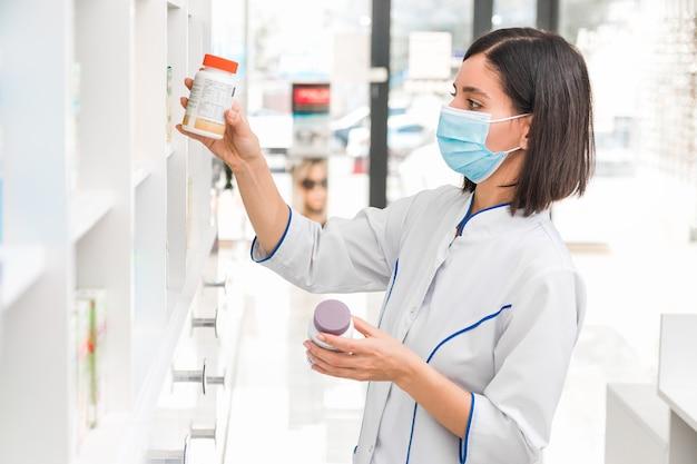 Het juiste medicijn kiezen. professioneel uitziende vrouwelijke apotheker met medisch masker op in drogisterij die de prospectus van een nieuw medicijn bestudeert.