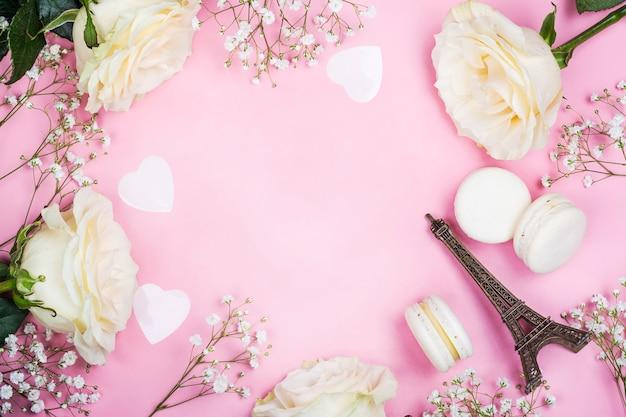 Het kader van de valentijnskaartendag met witte bloemen op roze