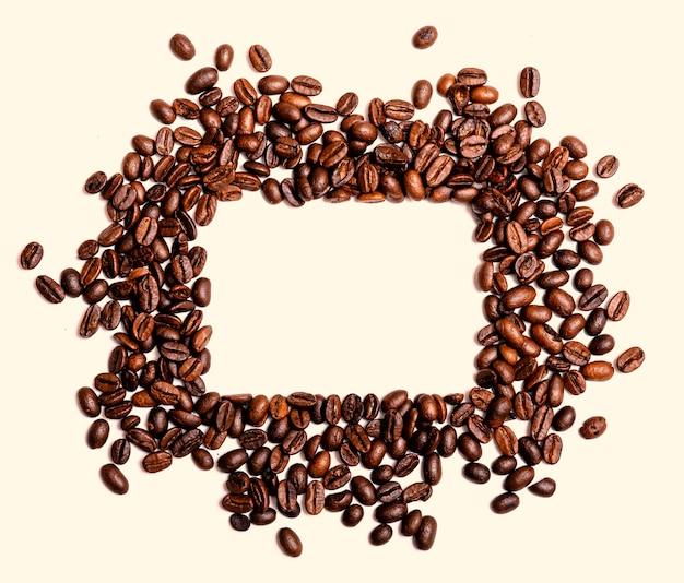 Het kader van geroosterde bruine die koffiebonen op wit worden geïsoleerd kan als achtergrond of textuur gebruiken.
