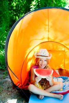 Het kamperen kinderenmeisje die in tent watermeloenplak eten