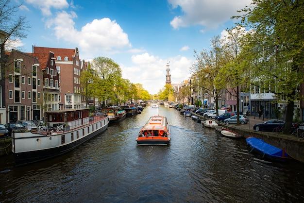 Het kanaal van amsterdam met cruiseschip met het traditionele huis van nederland in amsterdam