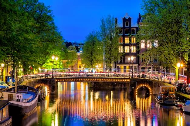 Het kanaal van amsterdam met typische nederlandse huizen en brug tijdens schemering blauw uur in holland, nederland.