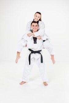 Het karatemeisje en de jongen in witte kimono en zwarte band poseren over grijze achtergrond.