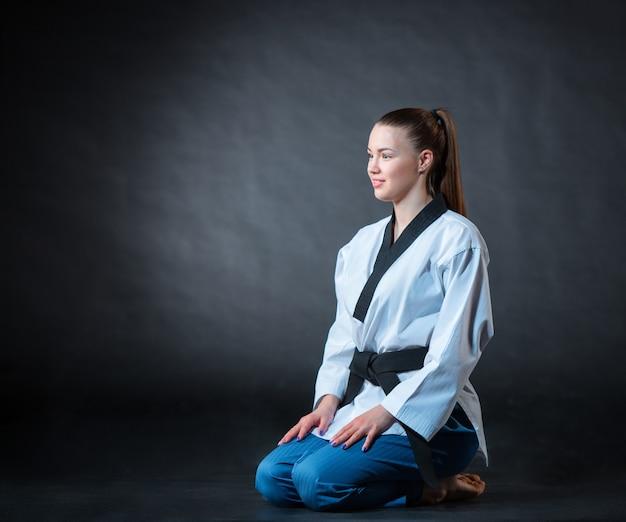 Het karatemeisje in witte kimono en zwarte band die karate opleidt over grijze achtergrond.