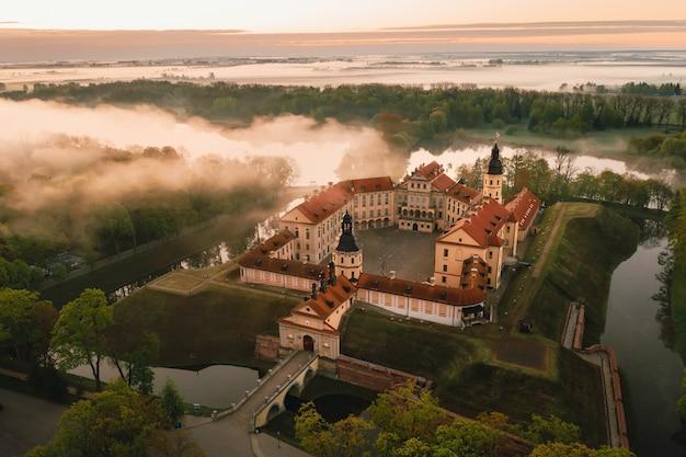 Het kasteel van nesvizh is een residentieel kasteel van de familie radziwill in nesvizh, wit-rusland, met een prachtig uitzicht van bovenaf bij zonsopgang.
