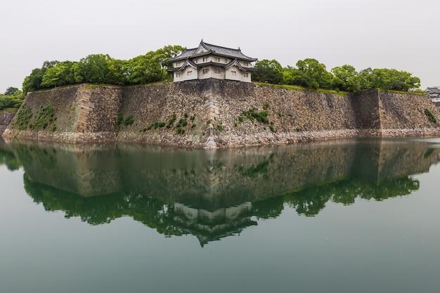 Het kasteelmuren die van osaka in water nadenken