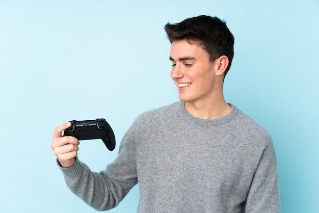 Het kaukasische de mens van de tiener spelen met een videospellingscontrolemechanisme dat op blauwe achtergrond met gelukkige uitdrukking wordt geïsoleerd