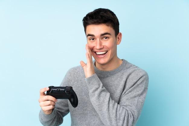 Het kaukasische de mens van de tiener spelen met een videospellingscontrolemechanisme dat op blauwe achtergrond wordt geïsoleerd die iets fluistert