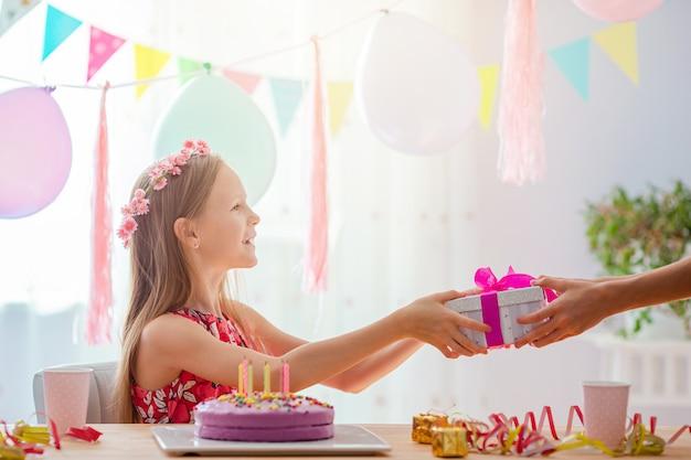 Het kaukasische meisje glimlacht dromerig. feestelijke kleurrijke achtergrond met ballonnen. verjaardagsfeestje en wensen concept.
