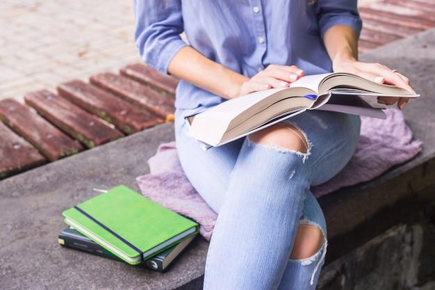 Het kaukasische meisje leest een dik onderwijsboek terwijl openlucht het zitten