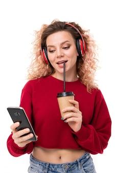 Het kaukasische meisje met krullend eerlijk haar drinkt koffie en babbelend met vrienden, geïsoleerd portret