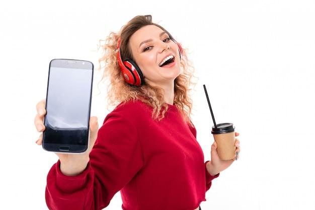 Het kaukasische meisje met krullend eerlijk haar drinkt koffie, luistert aan muziek en toont haar telefoon, geïsoleerd portret