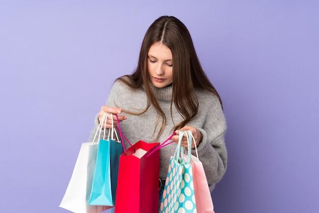 Het kaukasische meisje van de tiener dat op purpere het winkelen zakken wordt geïsoleerd en binnen het kijkt