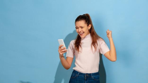 Het kaukasische portret van het tienermeisje dat op blauw wordt geïsoleerd