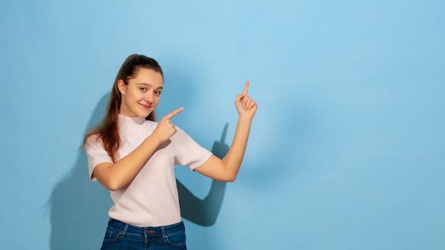 Het kaukasische portret van het tienermeisje dat op blauwe studio wordt geïsoleerd