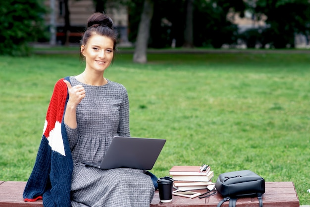 Het kaukasische studentenmeisje gebruikt laptop en toont duim bij het park.